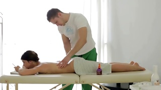 Brunette sexually hot young woman getting her body massaged